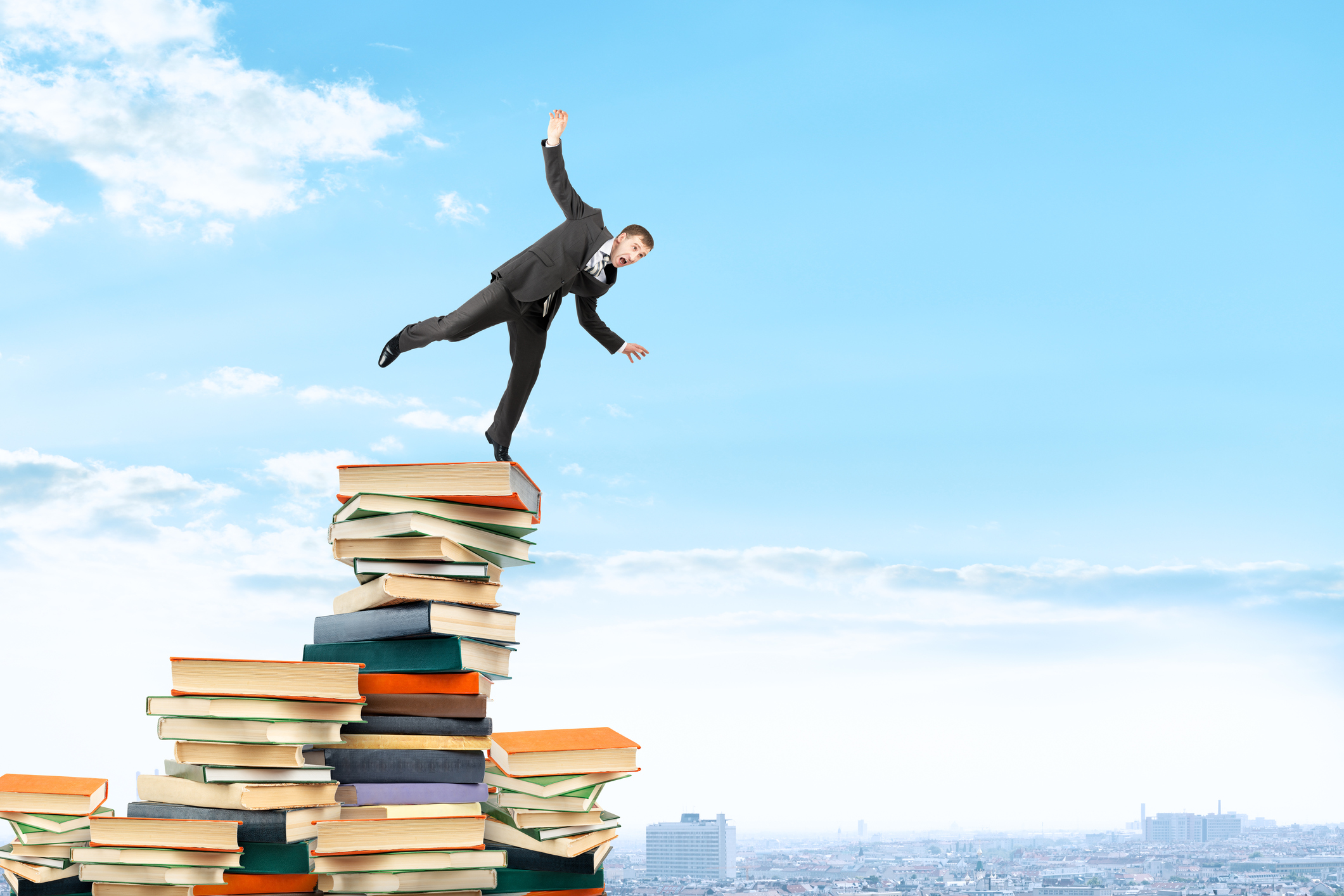 Businessman on pile of books trying not to fall, business concept